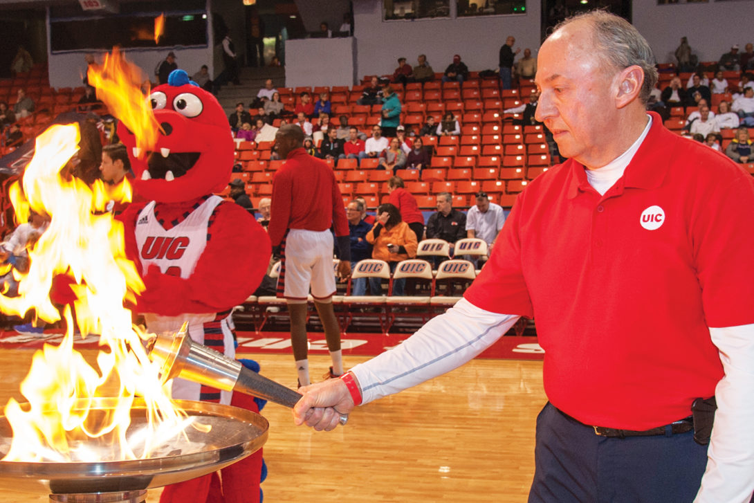 an alumnus lights the flame at a basketball game