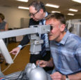 Marty Cless, son of Gerhard Cless, looks through one of the simulation microscopes as Dr. Mark Rosenblatt, professor and head of ophthalmology and visual sciences in the UIC College of Medicine, looks on. (Photo: Diane Smutny)