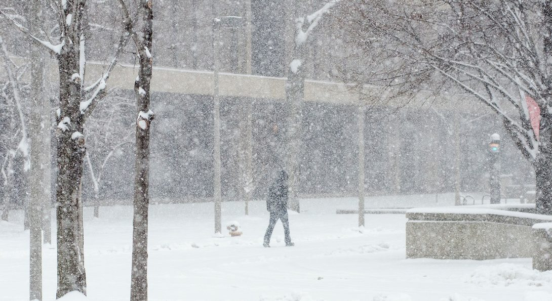 student walks on campus in snowstorm