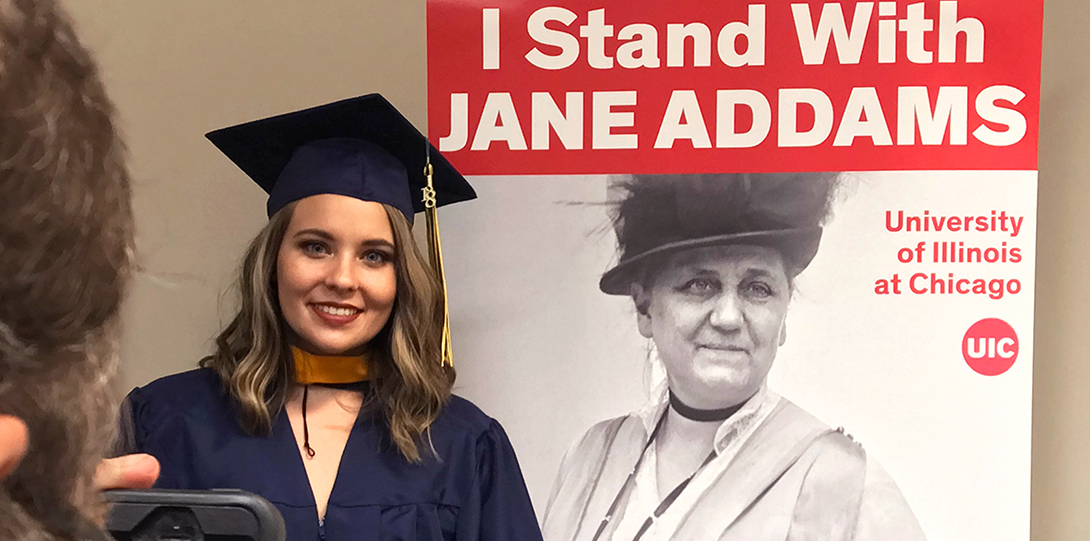 2018 Spring Commencement - JACSW grad poses with Jane Addams poster