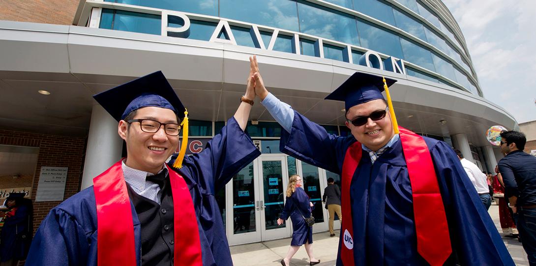 2018 Spring Commencement - graduates high five outside Pavilion