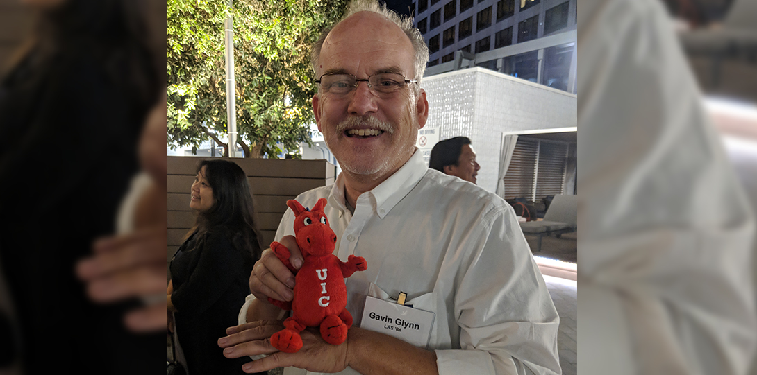alumnus holding up a sparky doll