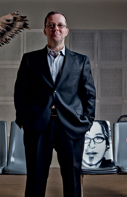 Photo of UIC alumnus and artist Jim Duignan standing in front of a portrait of UIC alumnus and artist Mike Piazza