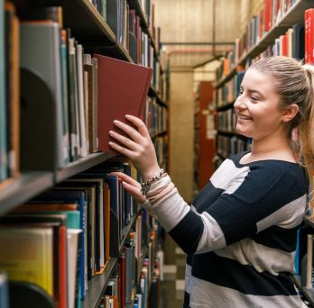 A girl in the library removing a book from the shelf