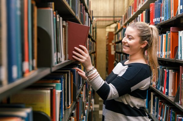 student in a library removing a book from the shelf