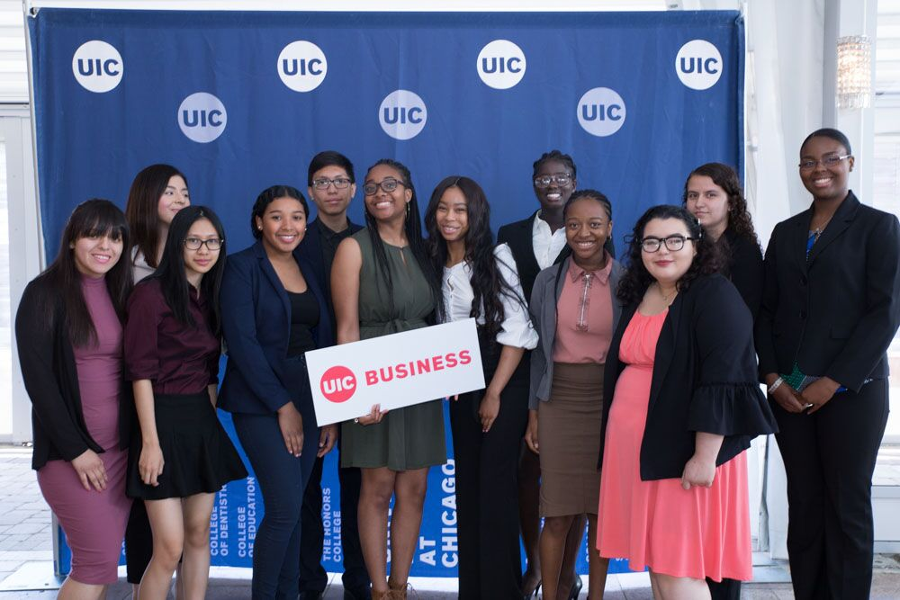 A group of students standing in front of a UIC backdrop holding a UIC Business sign