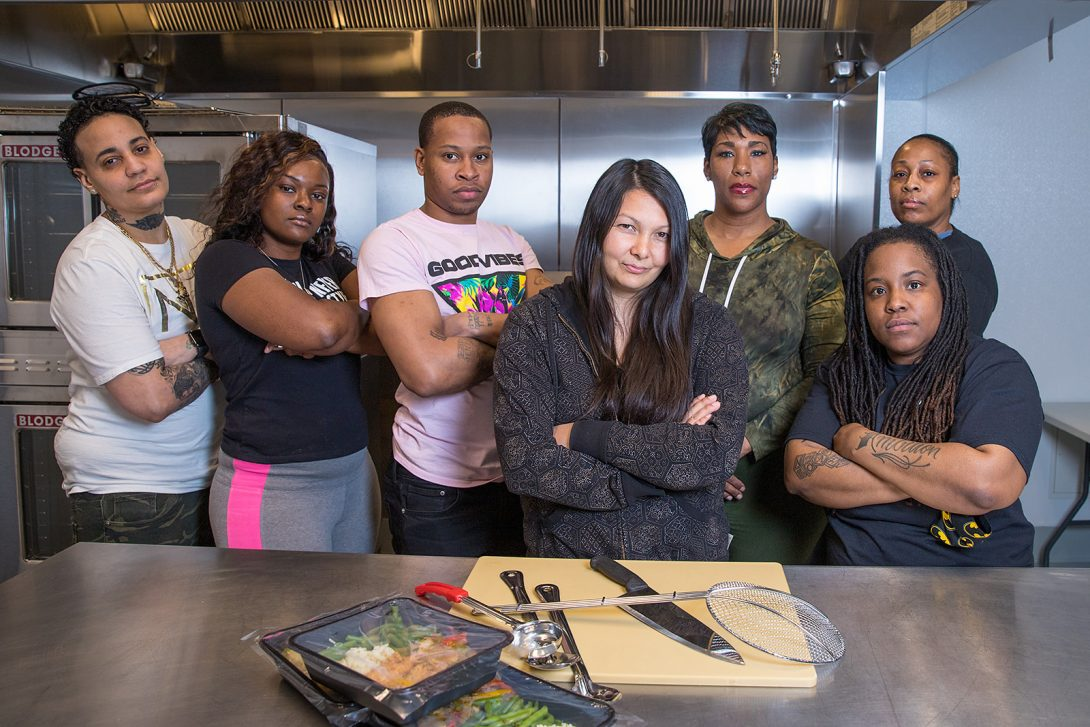 seven people standing behind a chef's table posing for the camera