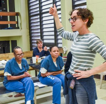 A woman speaking to other women in prison