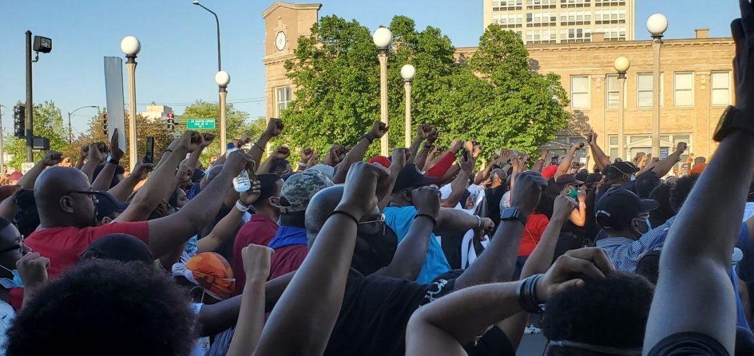People kneeling with fists raised