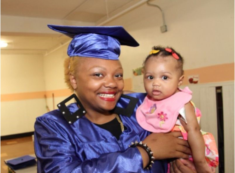 Woman in graduation gown holding a baby