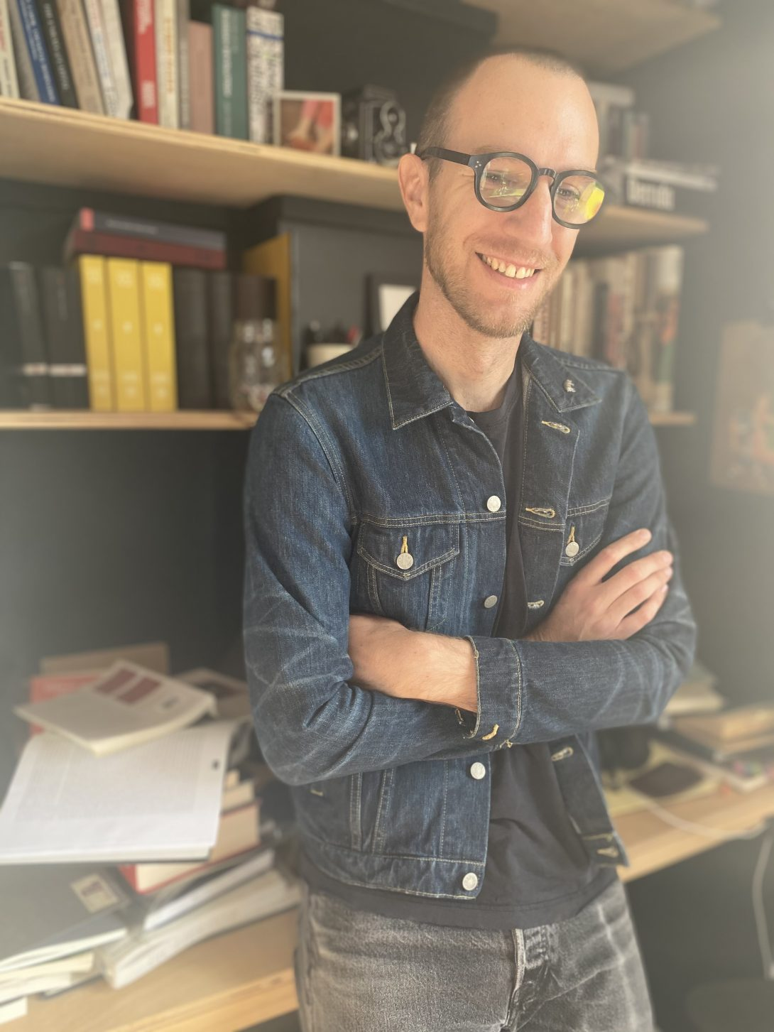 A person standing in front of bookshelf smiling