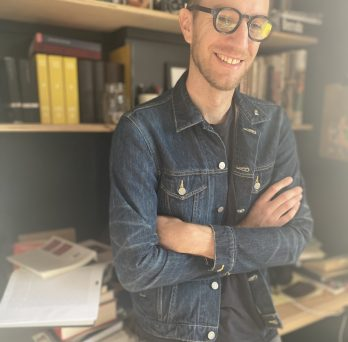 Person standing in front of a bookshelf smiling for the camera